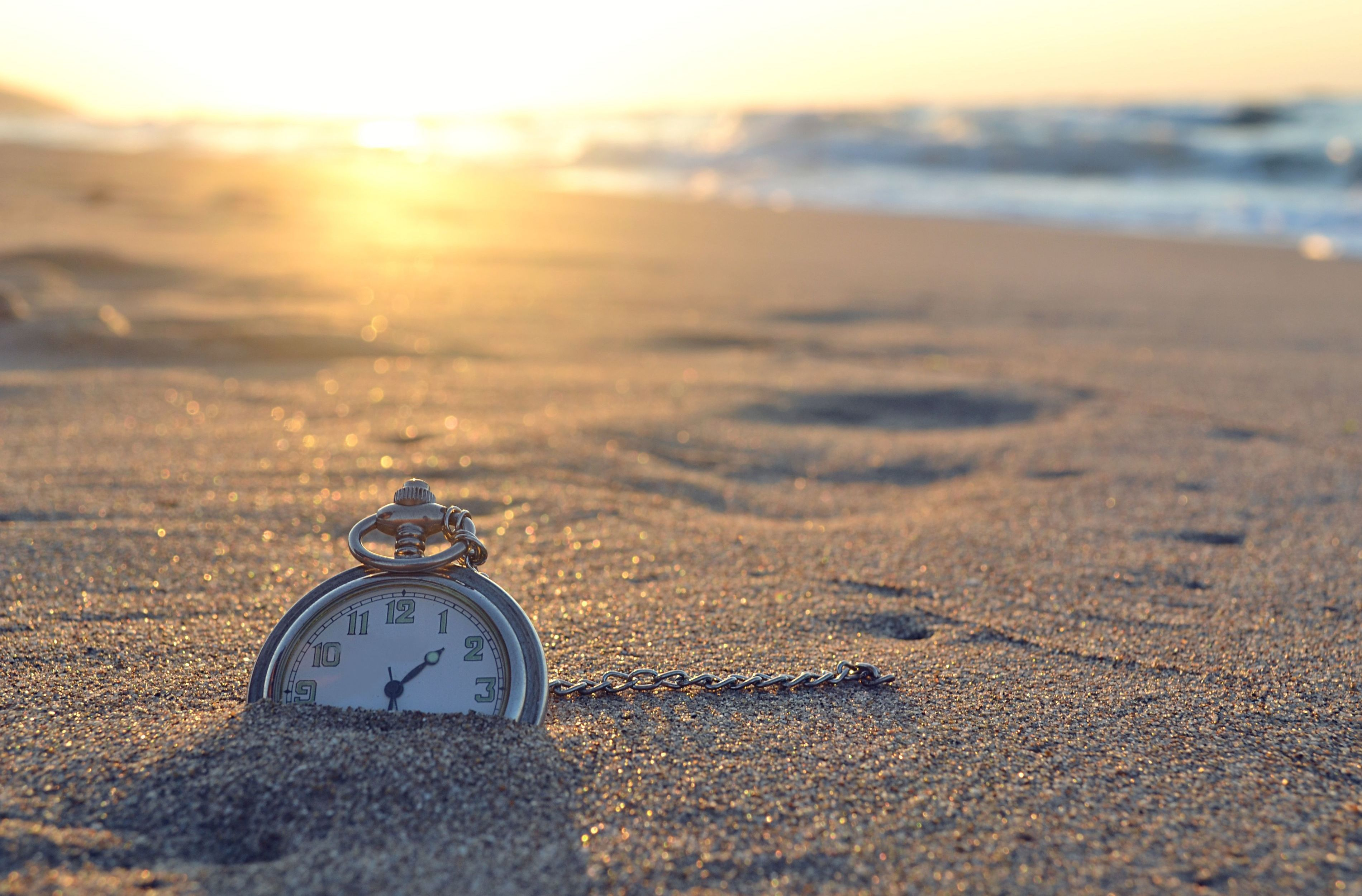 Pocket watch on the beach the meaning of time leaving its footprints