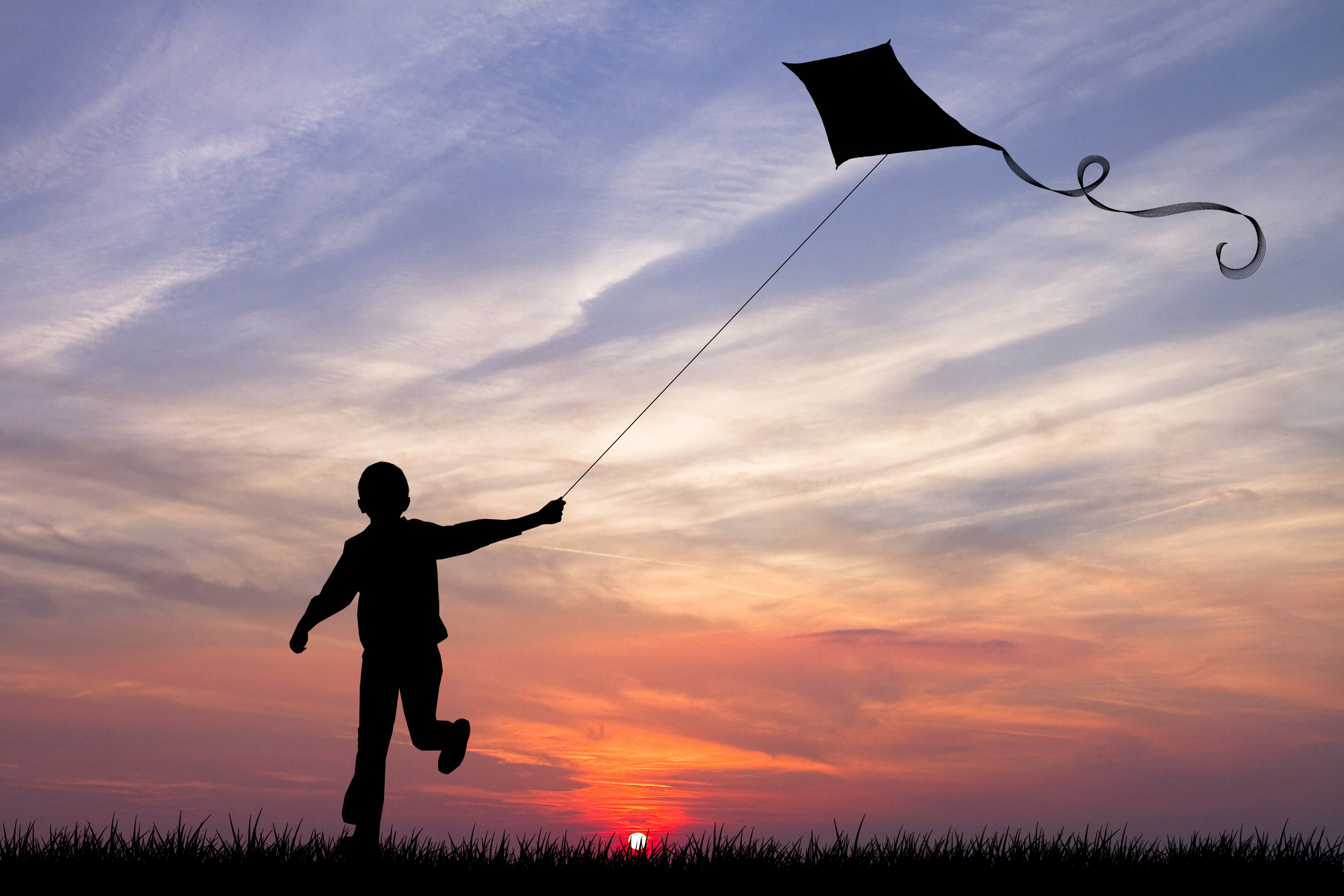 Boy with flying kite running towards the sunset at the horizon