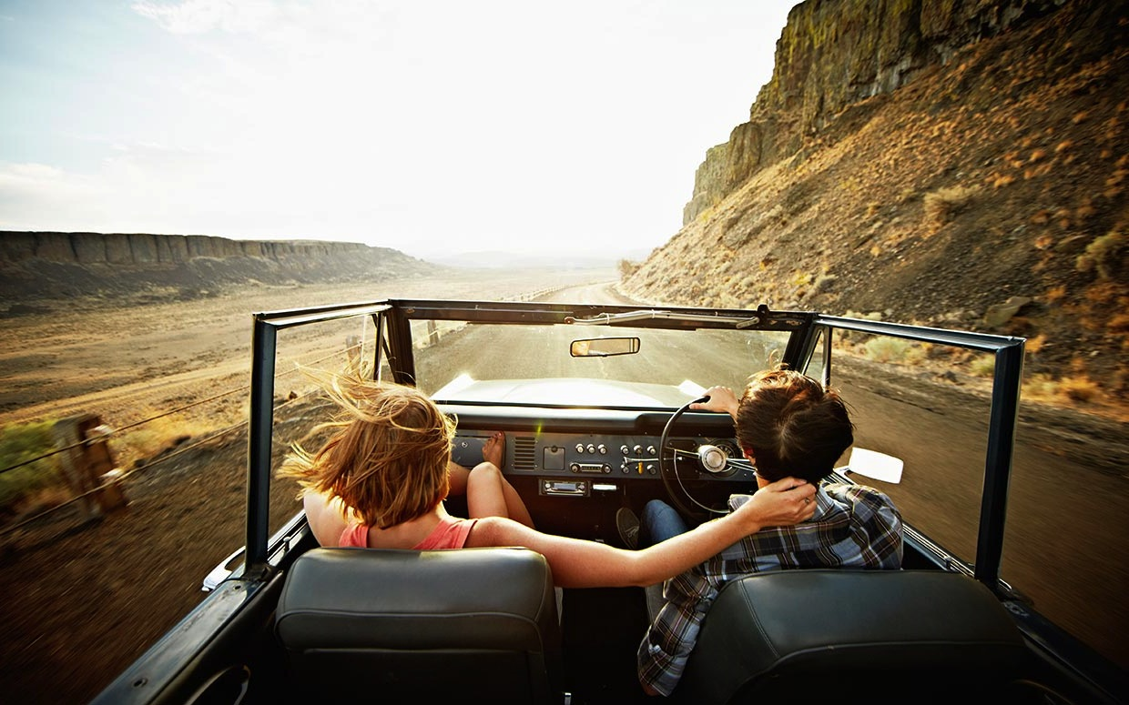 Couple in convertible driving holiday on empty roads bespoke trip