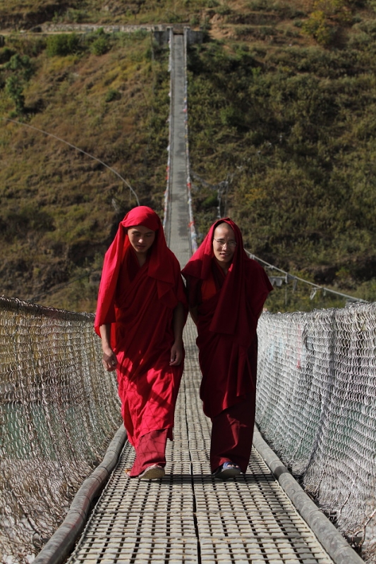 Punakha Valley suspension bridge bulit by ingenious locals above mountain river red-robed monks