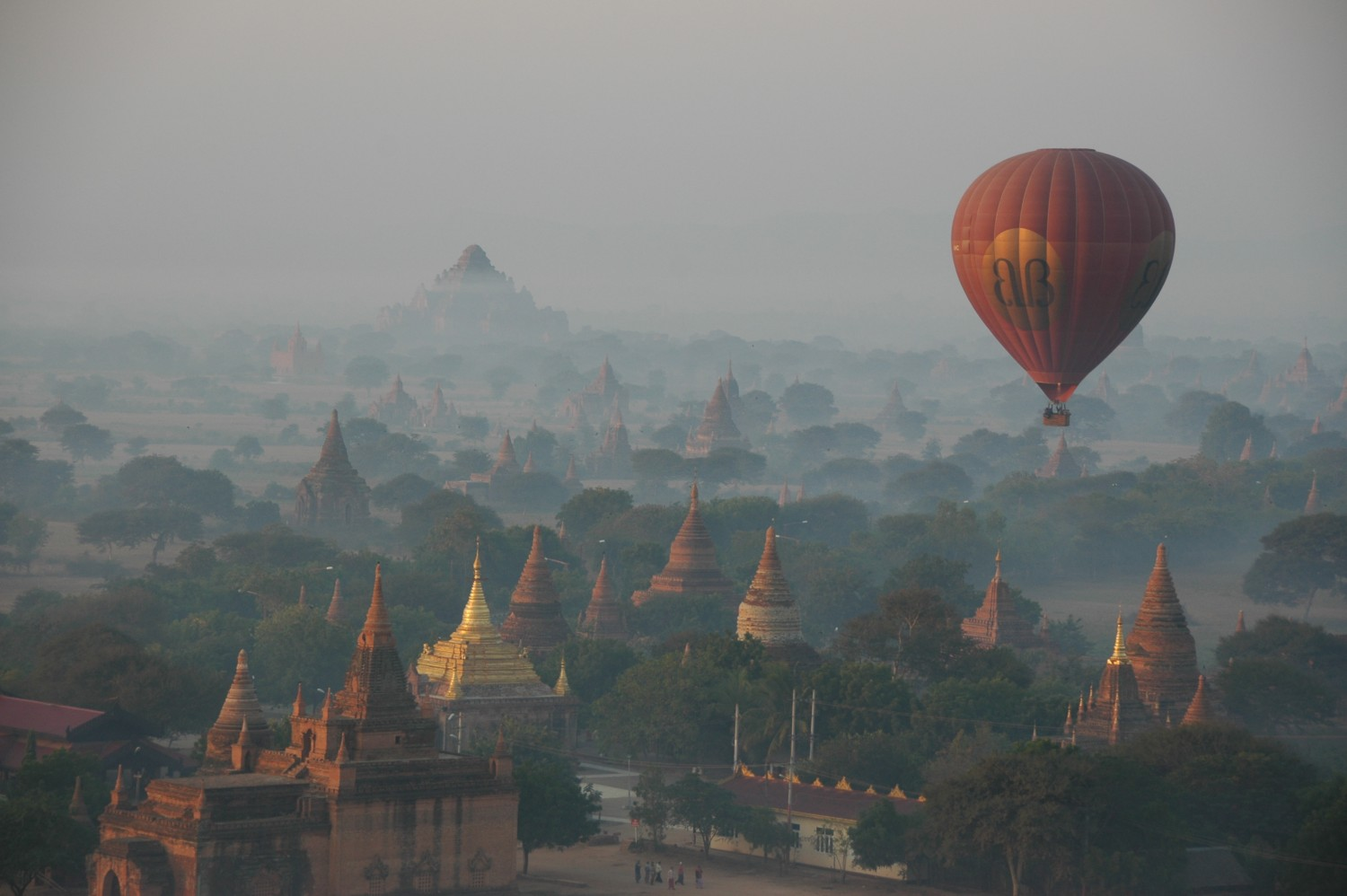 Hot-air balloons flying over mystical foggy Bagan Myanmar