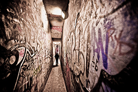 Narrow dark alley surrounded by graffiti sprayed walls discover the secrets at the end