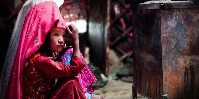 Kirghiz girl in yurt, taking refuge next to a stove, in Afghanistan