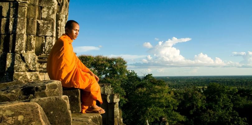 Monk sitting on a rock overlooking the abyss in Bayon, Cambodia