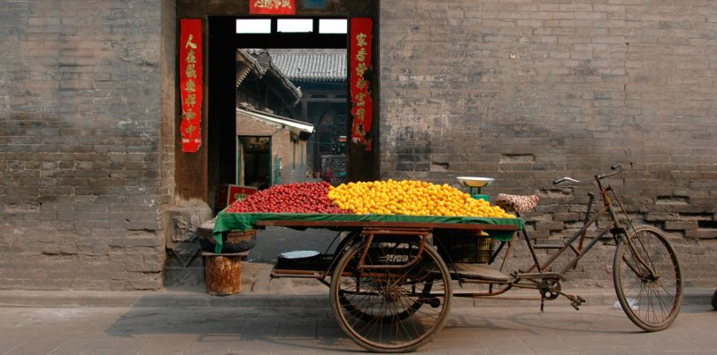 Loaded bicycle in front of a wall in Pingyao, China