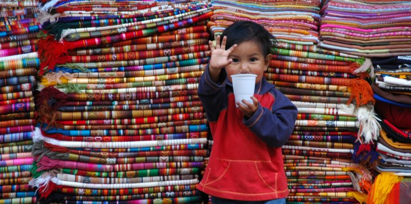Little child with cup standing in front of textiles in Ecuador