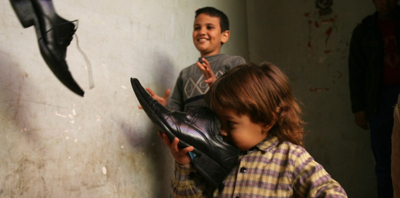 Boys sniffing and playing with shoes