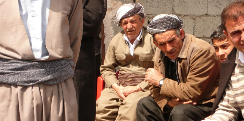 Iraqi men sitting outside on a bench