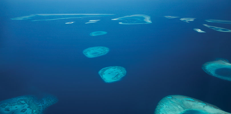 View down on Maldive islands from plane discover the Indian Ocean