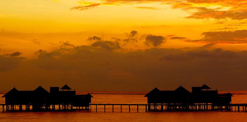 Maldives sunset wide ocean huts on stilts