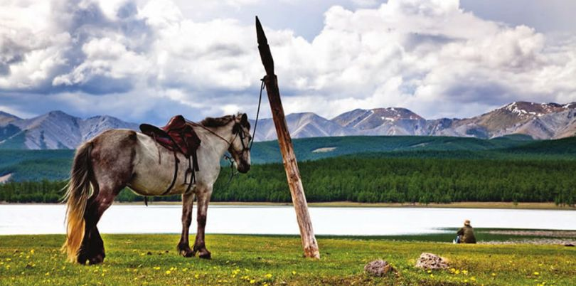 Horse overlooking its rider by a lake, Mongolia