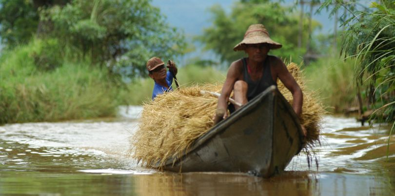 Two men in a boat with crops, Myanmar