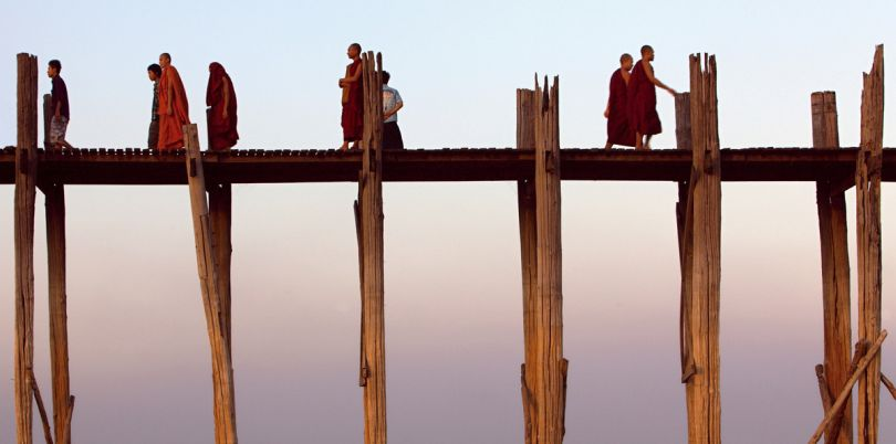 Monks walking over a bridge on stilts in Myanmar