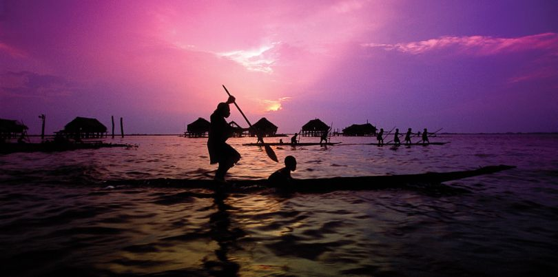 Rowers in a boat sailing around houses on stilts at dawn in Papua New Guinea