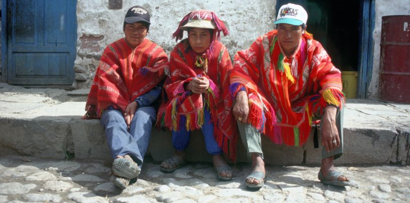 Poncho men sitting on pavement in Cusco Peru