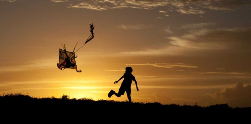Child flying a kite in the sunset, Sri Lanka